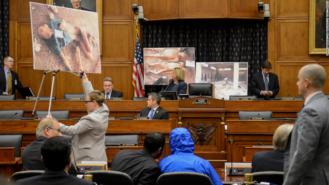 """Photographs of victims of the Assad regime are displayed as a Syrian army defector known as """"Caesar,"""" center, appears in disguise to speak before the House Foreign Affairs Committee in Washington. The July 31, 2014, briefing was called """"Assad's Killing Machine Exposed: Implications for U.S. Policy."""" Caesar, apparently a witness to the regime's brutality, has <a href=""""http://ift.tt/1j22ufc; target=""""_blank"""">smuggled more than 50,000 photographs</a> depicting the torture and execution of more than 10,000 dissidents. CNN cannot independently confirm the authenticity of the photos, documents and testimony referenced in the report."""