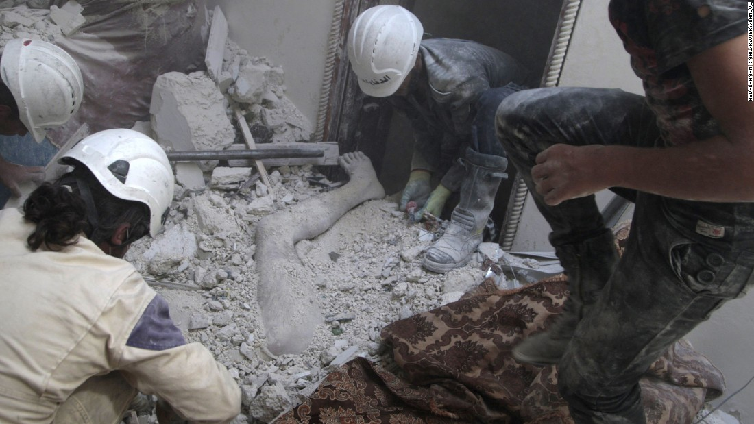 """Volunteers remove a dead body from under debris after shelling in Aleppo on August 29, 2014. According to the Syrian Civil Defense, barrel bombs are now the greatest killer of civilians in many parts of Syria. <a href=""""http://ift.tt/1WcUBSk; target=""""_blank"""">The White Helmets</a> are a humanitarian organization that tries to save lives and offer relief."""
