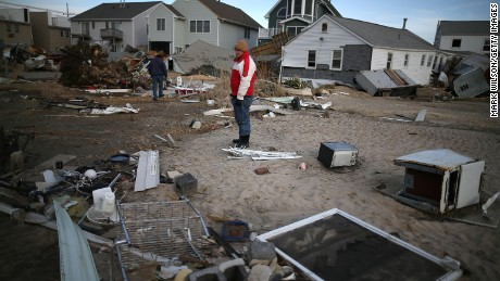 David Mccue (C), looks for pieces of his beach house that was completely demolished by Superstorm Sandy on November 25, 2012 in Seaside Heights, New Jersey.  s)