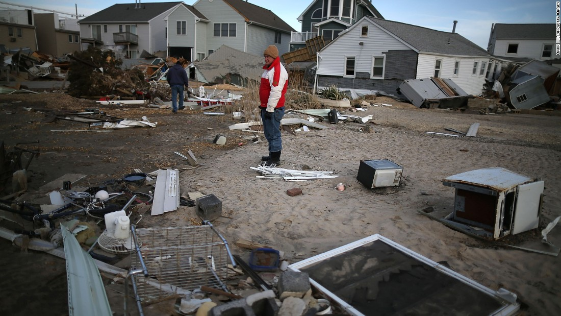"<strong>Sandy, 2012:</strong> It technically lost its hurricane status shortly before striking New Jersey, but its gigantic size -- it covered 1.8 million square miles at landfall -- sent devastating storm surges to the coast. Here, a man looks for pieces of his beach house after <a href=""http://www.cnn.com/2013/07/13/world/americas/hurricane-sandy-fast-facts/"">Sandy </a>demolished it in Seaside Heights, New Jersey. With 72 directly killed in eight states, this was the most deadly tropical cyclone outside the South since 1972's Hurricane Agnes. At least 650,000 U.S. homes were damaged or destroyed in the U.S."