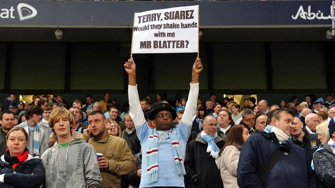 A Manchester City fan displays a banner with a message for FIFA President Sepp Blatter regarding his handling of  allegations of racism in football in 2011. Blatter had earlier suggested that incidents of racism on the pitch could be sorted out with a handshake when a game finished.