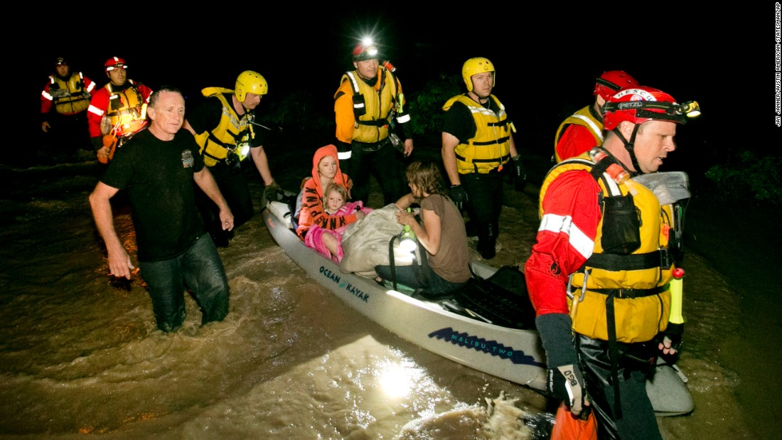 Retha Norris, Ally Smith and Christina Norris, all seated in the canoe, are rescued by firefighters on May 24 after they clung to a tree in Kyle, Texas.