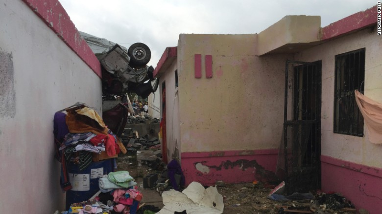 A vehicle lies on the rooftop of a home.