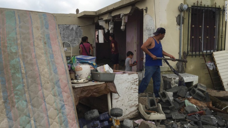 Residents clear away debris from their home.