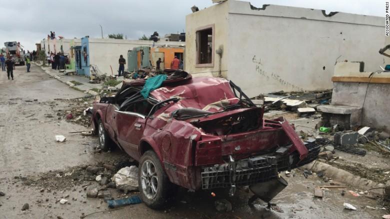A damaged car sits on a road.