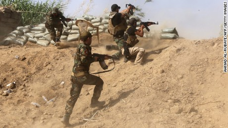 Iraqi Sunni fighters battling Islamic State (IS) group jihadists alongside government forces fire their weapons on the outskirts of Iraq's Baiji oil refinery, about 200 kilometres north of Baghdad, on May 25, 2015