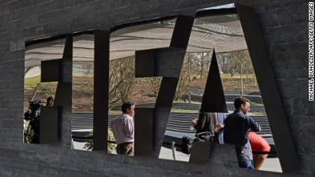 Caption:Member of the media wait next to a logo of the Worlds football governing body, at the FIFA headquarters in Zurich, prior to a press conference of FIFA President Sepp Blatter on March 20, 2015, closing a two-day meeting to decide the dates of the 2022 World Cup in Qatar. AFP PHOTO / MICHAEL BUHOLZER (Photo credit should read MICHAEL BUHOLZER/AFP/Getty Images)