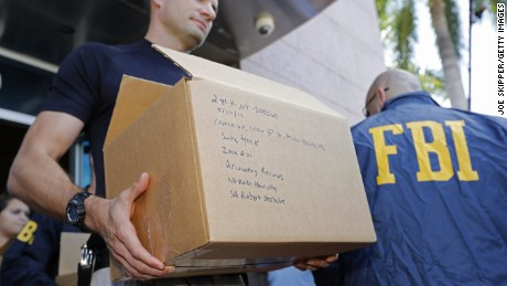 FBI agents carry boxes from the headquarters of CONCACAF after it was raided on May 27, 2015 in Miami Beach, Florida. The raid is part of an international investigation of FIFA where nine FIFA officials and five corporate executives were charged with racketeering, wire fraud and money laundering conspiracies.