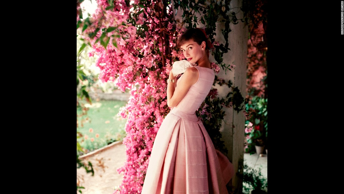 "Hepburn poses at her rented farmhouse near Rome in this 1955 photo by Norman Parkinson. She is wearing a Givenchy cocktail dress from the Spring/Summer 1955 collection. ""The narrow waist and full pleated skirt of the dress are typical of the 'New Look' silhouette which was so popular in the post-war period,"" Trompeteler wrote."