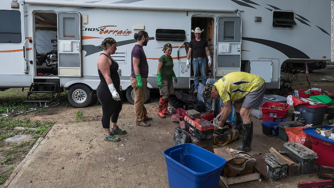 Butch Neuenschwander, right, looks for things to salvage from his RV, which was flooded in San Marcos, Texas, on Wednesday, May 27.