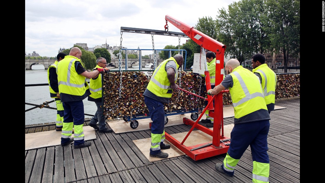 Paris city employees remove a railing loaded with locks on the Pont des Arts bridge on Monday, June 1. For years, couples have put locks on the bridge to symbolize their affection -- a tradition often followed by throwing the key into the Seine River below. But the city is now removing the padlocks because sections of the bridge's fencing started crumbling under the locks' weight.