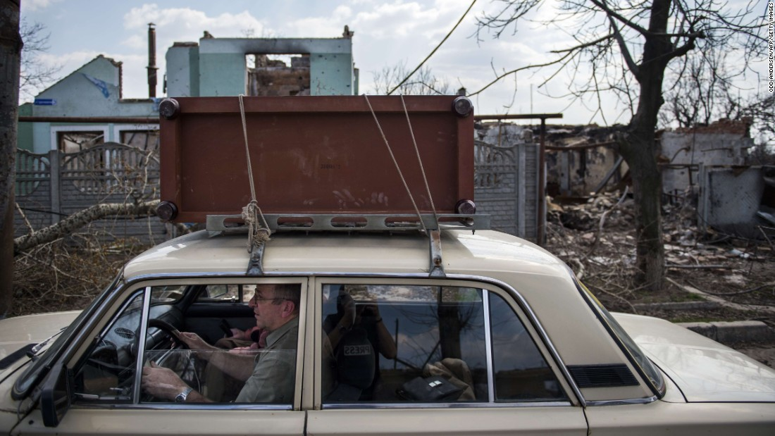 Residents flee with salvaged belongings during renewed fighting in the Jabunki neighborhood near the airport in Donetsk on Monday, April 13.