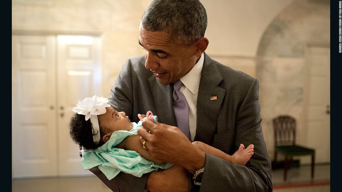 Obama holds the daughter of former staff members Darienne Page Rakestraw and London Rakestraw at the White House in July.