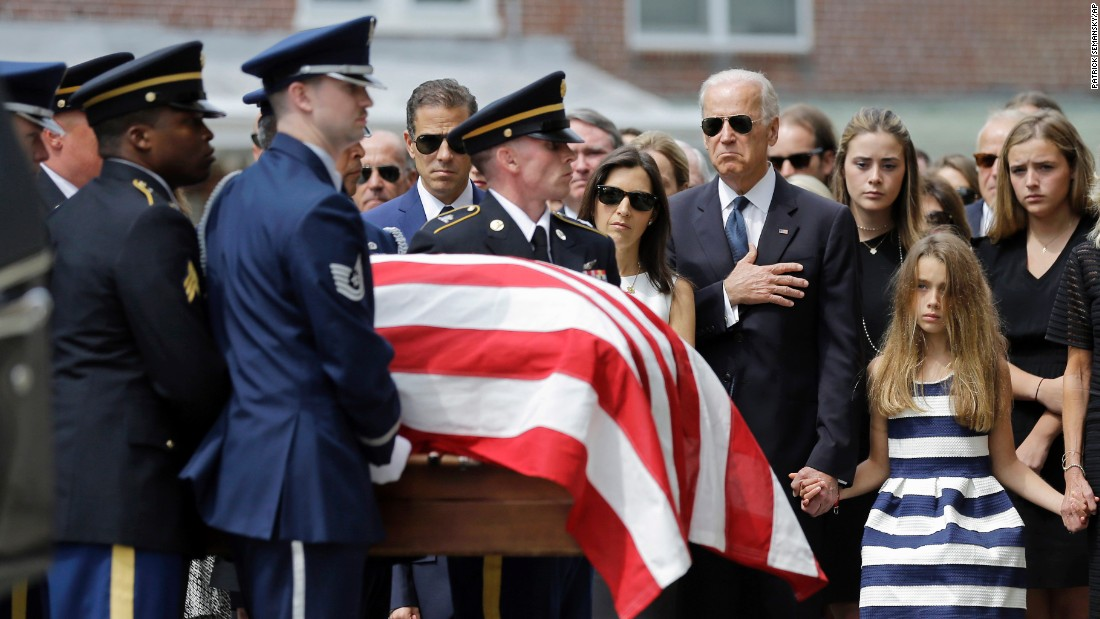 Vice President Joe Biden, accompanied by his family, holds his hand over his heart as he watches an honor guard carry a casket containing the remains of his son into St. Anthony of Padua Roman Catholic Church in Wilmington, Delaqare, on June 6. Standing alongside the vice president are Beau Biden's widow Hallie Biden, left, and daughter, Natalie.