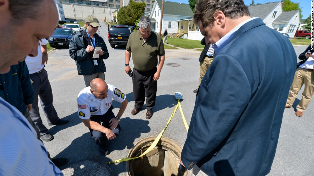 Officials look at the manhole through which the inmates crawled to freedom.