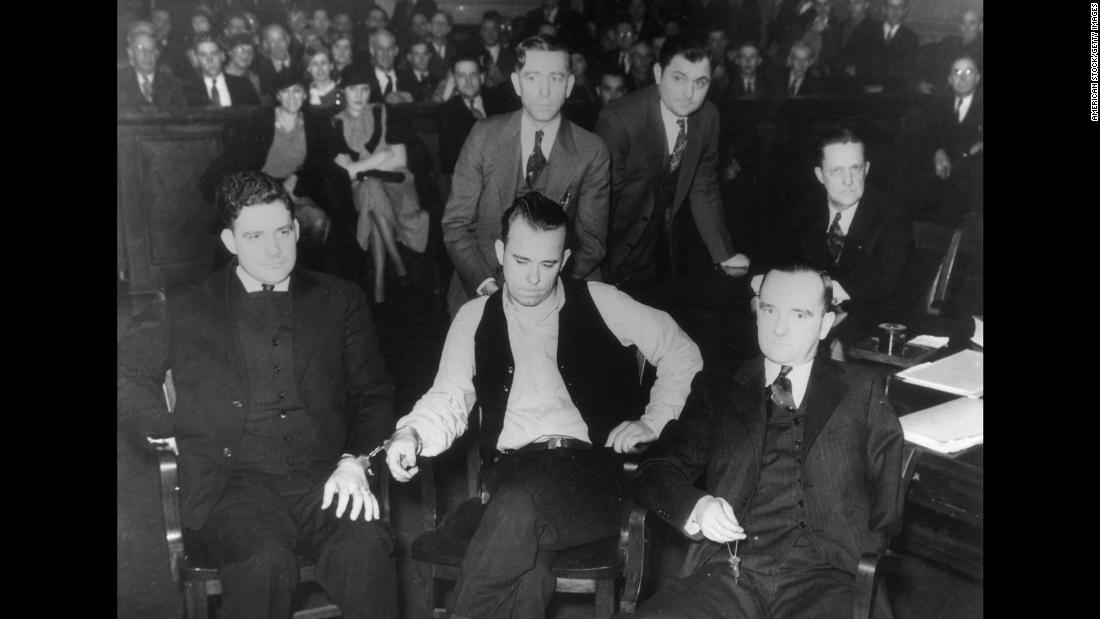 American criminal John Dillinger, center, sits in court in 1934 after being accused of killing a police officer. Later that year, he escaped an Indiana jail wielding a wooden gun he whittled. After imprisoning guards, he drove away in the sheriff's car. A few months later, he was shot dead outside of a theater in Chicago.
