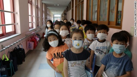 SEOUL, SOUTH KOREA - JUNE 09: Elementary school students wear masks as a precaution against the MERS virus as they wait for a lesson to start at Midong Elementary School on June 9, 2015 in Seoul, South Korea. South Korea has reported eight deaths related to the virus with 2,500 people quarantined and 1,800 schools closed as of June 9, 2015. (Photo by Chung Sung-Jun/Getty Images)