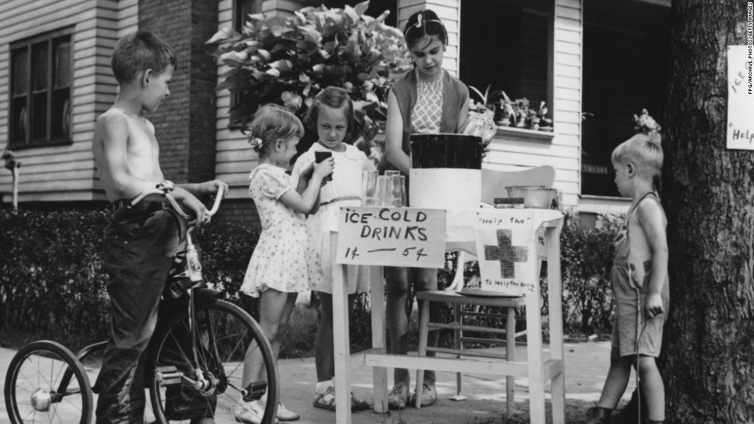 A girl runs a lemonade stand in front of her house circa 1955. A sign indicates that proceeds will go to the Red Cross.