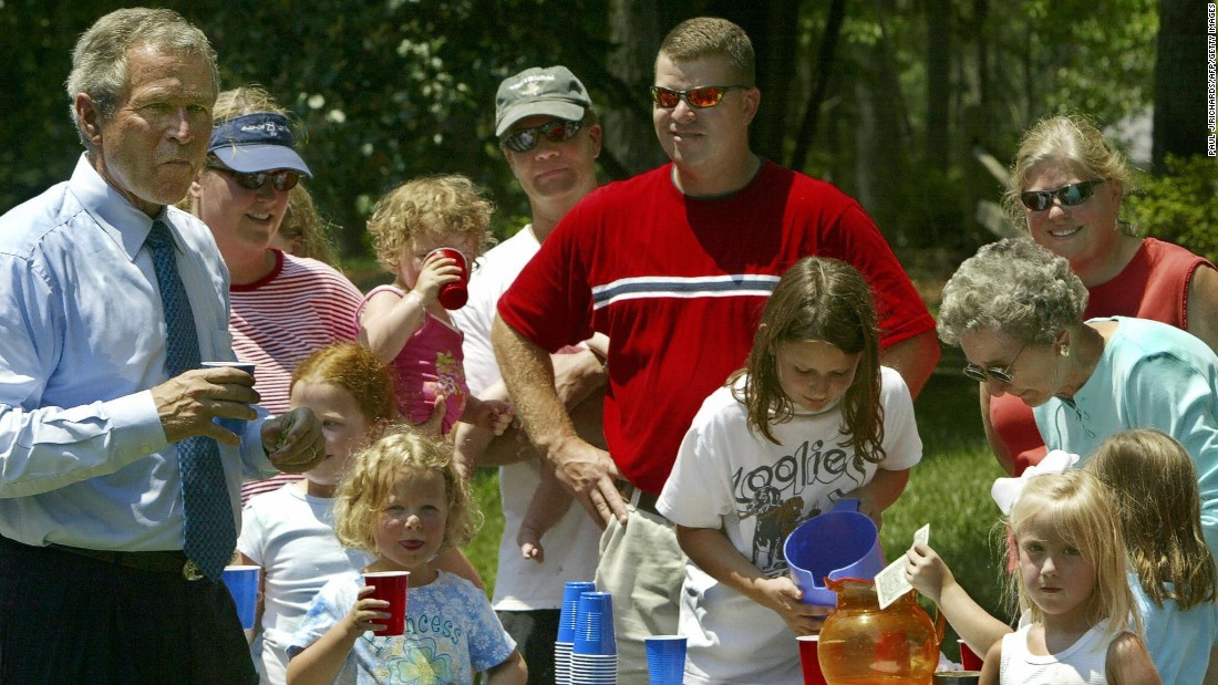 President George Bush, while traveling to Raleigh-Durham International Airport in North Carolina, stops for a lemonade at a roadside stand run by a local firefighter and his family in July 2004.
