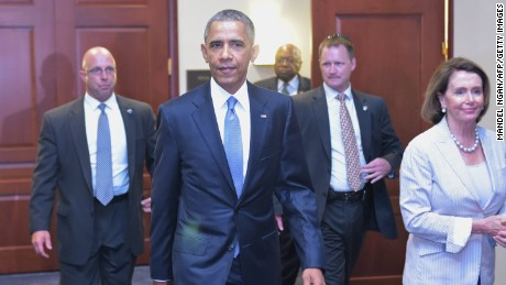 U.S. President Barack Obama and House Minority Leader Nancy Pelossi walk through a hallway after meeting with House Democrats at the US Capitol on June 12, 2015 in Washington, D.C.