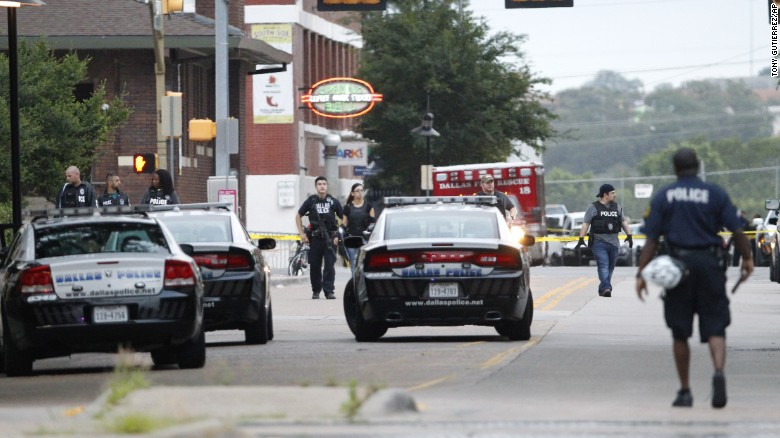 Dallas police officers walk down Belleview Street one block away from police headquarters as they search the area.