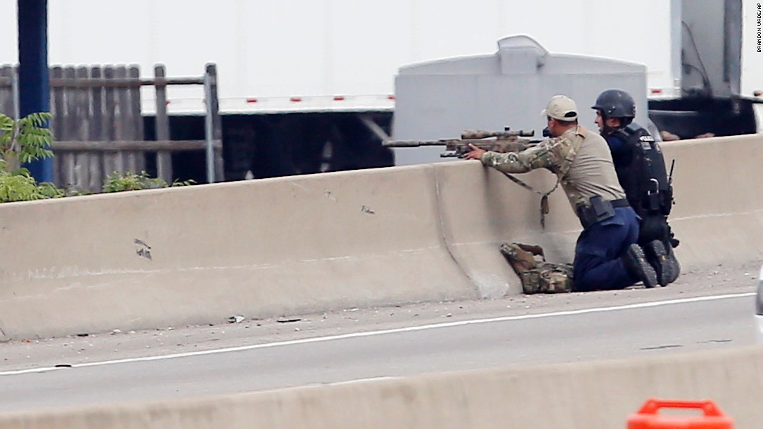 A sniper and a tactical officer take up positions on the shoulder of Interstate 45 at Dowdy Ferry Road.