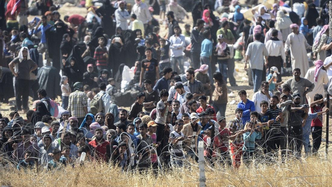 "Syrians fleeing fighting in Tal Abyad ask for water as they gather at a border crossing on the Syrian side of the border with Turkey. ""I haven't seen any refugees coming like this before in four years,"" said Kilic."