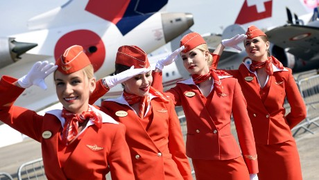 Cabin crew of the Russian airline Aeroflot salute as they walk past during the International Paris Airshow at Le Bourget on June 16, 2015