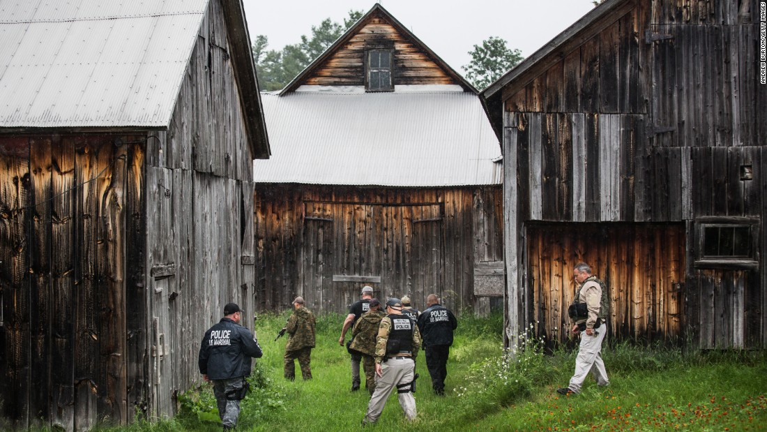 A task force of U.S. Marshals and police officers go door to door searching for the two escaped murderers on Tuesday, June 16, outside Dannemora, New York.
