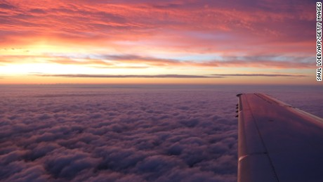 The sunrise is seen from an airplane window during a flight traveling over New Jersey, October 15, 2012. AFP PHOTO / Saul LOEB (Photo credit should read SAUL LOEB/AFP/Getty Images)