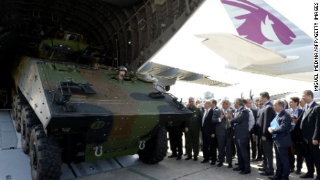 The Airbus A400M is a tactical airlifter which is used to transport military vehicles.  French officials look on as during the unloading of an armored military vehicle from the Airbus A400M at the Paris Airshow.