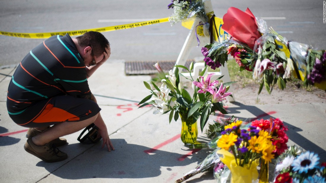 Charleston resident Noah Nicolaisen kneels at a makeshift memorial down the street from the church on June 18.
