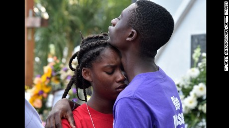 Two young people grieve outside Emanuel AME Church in Charleston, South Carolina, on June 19, 2015. Police captured the white suspect in a gun massacre at one of the oldest black churches in the United States, the latest deadly assault to feed simmering racial tensions. Police detained 21-year-old Dylann Roof, shown wearing the flags of defunct white supremacist regimes in pictures taken from social media, after nine churchgoers were shot dead during bible study on June 17. AFP PHOTO/MLADEN ANTONOV        (Photo credit should read MLADEN ANTONOV/AFP/Getty Images)