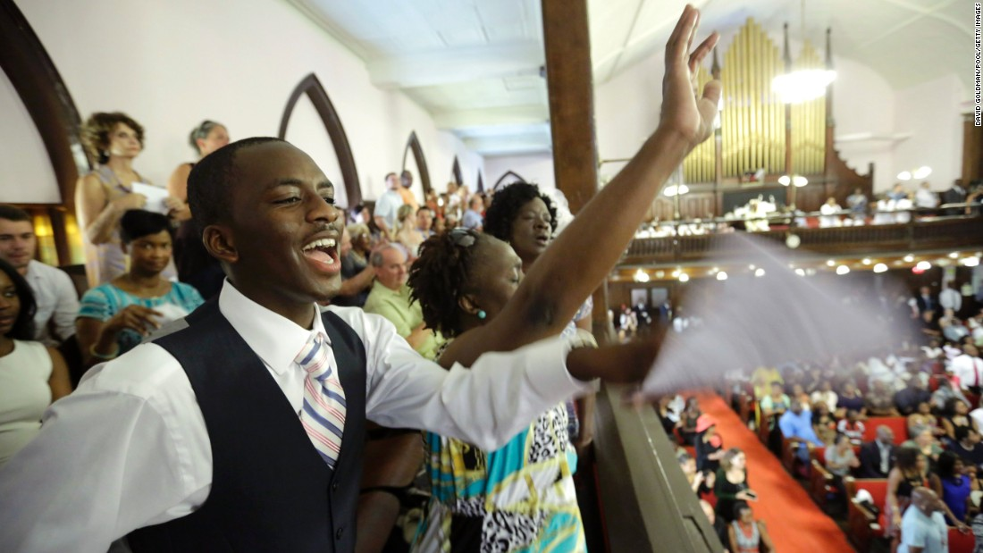 Parishioners Shakur Francis, left, and Karen Watson-Fleming sing as they attend the service.