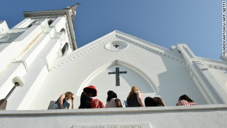 Caption:People line up to enter for Sunday service at the Emanuel AME Church in Charleston, South Carolina on June 21, 2015. Large crowds are expected at Sunday's service at the black church in Charleston where nine African Americans were gunned down, as a chilling website apparently created by the suspected white supremacist shooter emerged. The service will be the first since the bloodbath on Wednesday at the Emanuel African Methodist Episcopal Church in the southern state of South Carolina, which has fuelled simmering racial tensions in the United States and reignited impassioned calls for stronger gun-control laws. AFP PHOTO/ MLADEN ANTONOV (Photo credit should read MLADEN ANTONOV/AFP/Getty Images)