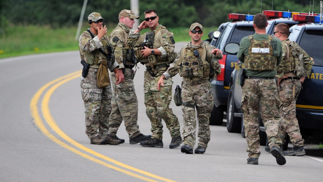 New York State Police officers gather along Route 20 near Friendship on June 21. About 300 law enforcement officers have searched the area.