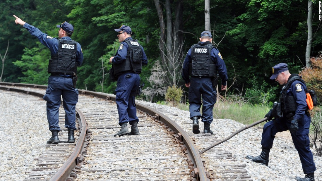 Corrections officers search railroad tracks near Friendship, New York, on Sunday, June 21, after a possible sighting of the fugitives.