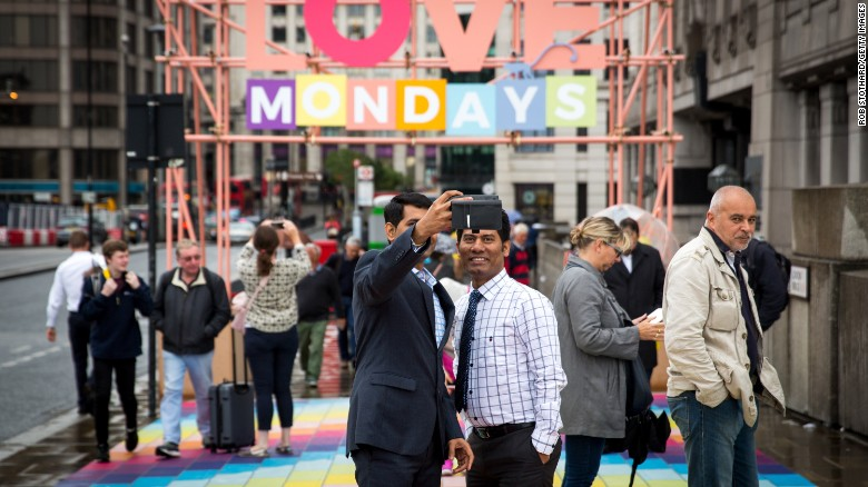 """Commuters across the London Bridge on Monday were met with a mosaic of colorful sidewalk tiles and a banner urging them to """"Love Mondays."""""""