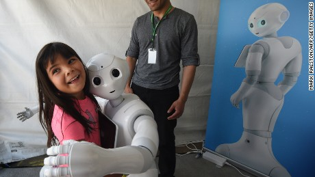 'Pepper,' a robot with emotional capabilities hugs a girl at DARPA Robotics Challenge on June 5, 2015.