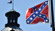 The South Carolina and US flags are seen flying at half-staff behind the Confederate flag erected in front of the State Congress building in Columbia, South Carolina on June 19, 2015. Police captured the white suspect in a gun massacre at one of the oldest black churches in Charleston in the United States, the latest deadly assault to feed simmering racial tensions. Police detained 21-year-old Dylann Roof, shown wearing the flags of defunct white supremacist regimes in pictures taken from social media, after nine churchgoers were shot dead during bible study on Wednesday. AFP PHOTO/MLADEN ANTONOV [Photo credit should read MLADEN ANTONOV/AFP/Getty Images)