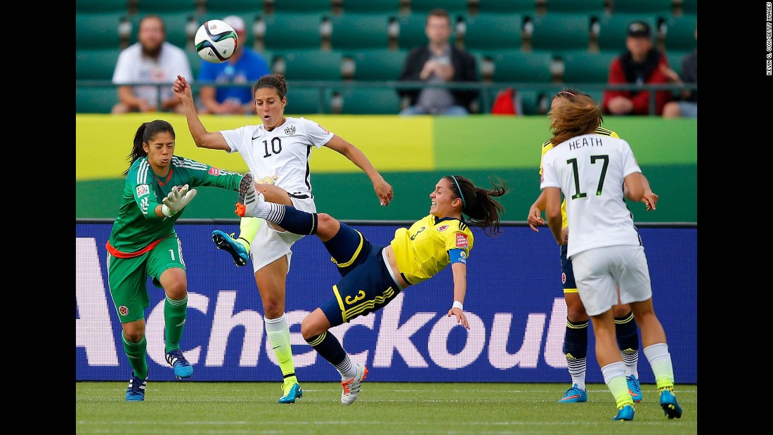 Lloyd goes for the ball between Colombia's Stefany Castano, left, and Natalia Gaitan.