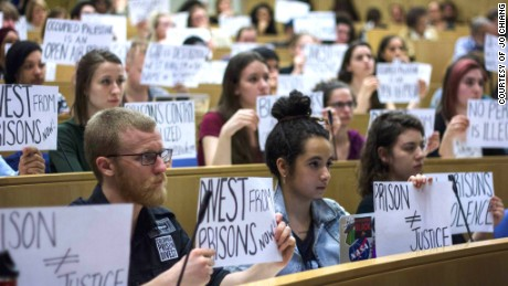 Members of Columbia Prison Divest hold protest signs at a University Senate meeting on April 2, 2015.