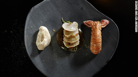 "Chilled blini creme, barbequed langoustine ""en gele,"" langoustine tataki and liquorice powder."