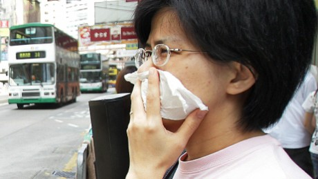 Hong Kong, CHINA:  A pedestrian covers her face with a tissue as she waits to cross a busy street in Hong Kong, 27 August 2006. Worsening pollution will sharply reduce Hong Kong's appeal to foreign investors, and most business leaders know people who are thinking of escaping the city due to the dirty air, a survey said 27 August. Nearly 80 percent of the 140 top executives polled felt Hong Kong's allure is falling, with four out of five knowing professionals who have considered leaving or have already left due to the air quality.    AFP PHOTO/TED ALJIBE  (Photo credit should read TED ALJIBE/AFP/Getty Images)