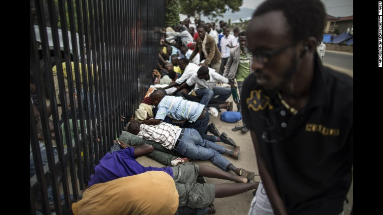 Burundian students slide under the main access gate of the US embassy compound in Bujumbura on June 25.