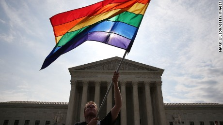 WASHINGTON, DC - JUNE 25: A gay marriage waves a flag in front of the Supreme Court Building June 25, 2015 in Washington, DC. The high court is expected rule in the next few days on whether states can prohibit same sex marriage, as 13 states currently do. (Photo by Mark Wilson/Getty Images)
