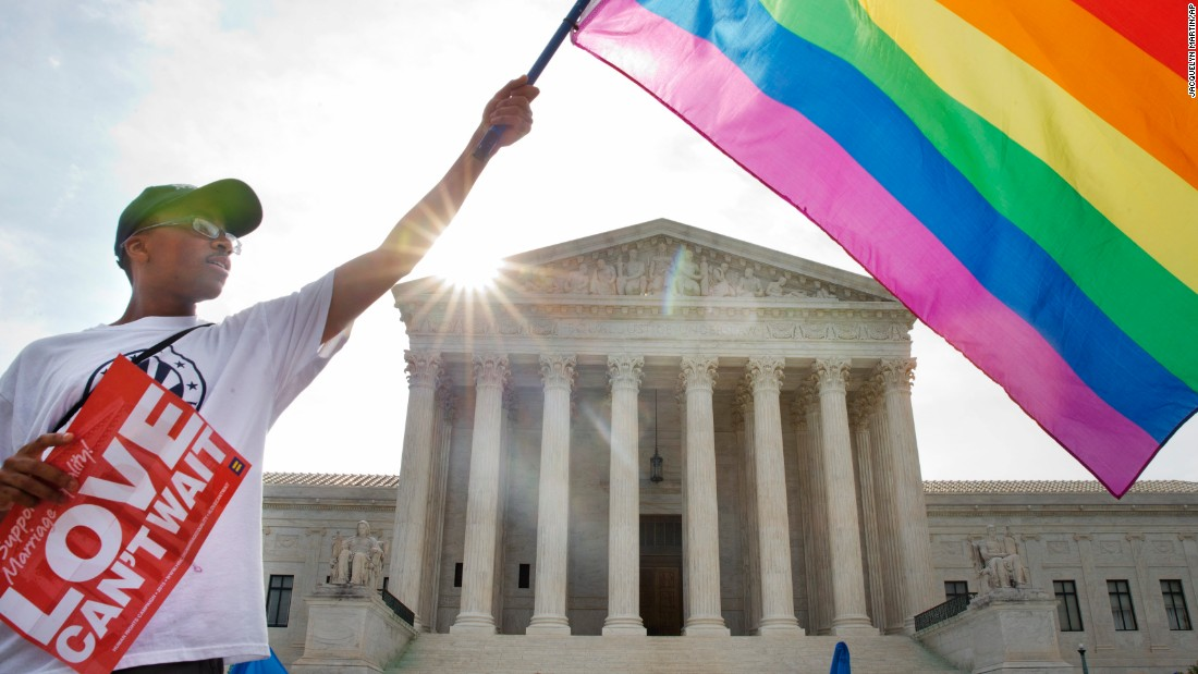 "Carlos McKnight of Washington waves a flag in support of same-sex marriage outside the U.S. Supreme Court on Friday, June 26. <a href=""http://www.cnn.com/2015/06/26/politics/supreme-court-same-sex-marriage-ruling/index.html"">The Supreme Court ruled 5-4</a> that states cannot ban same-sex marriage, handing gay rights advocates their biggest victory yet. See photos from states that approved same-sex marriage before the nationwide ruling:"