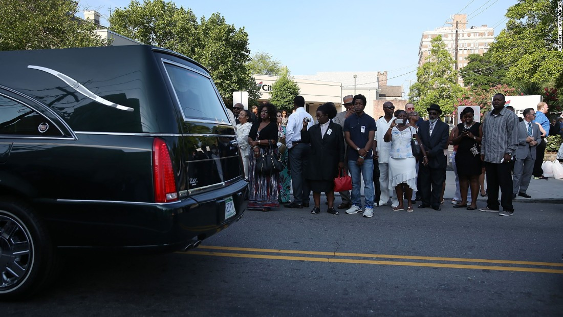 People watch as the hearse carrying Pinckney passes by June 26 in Charleston.