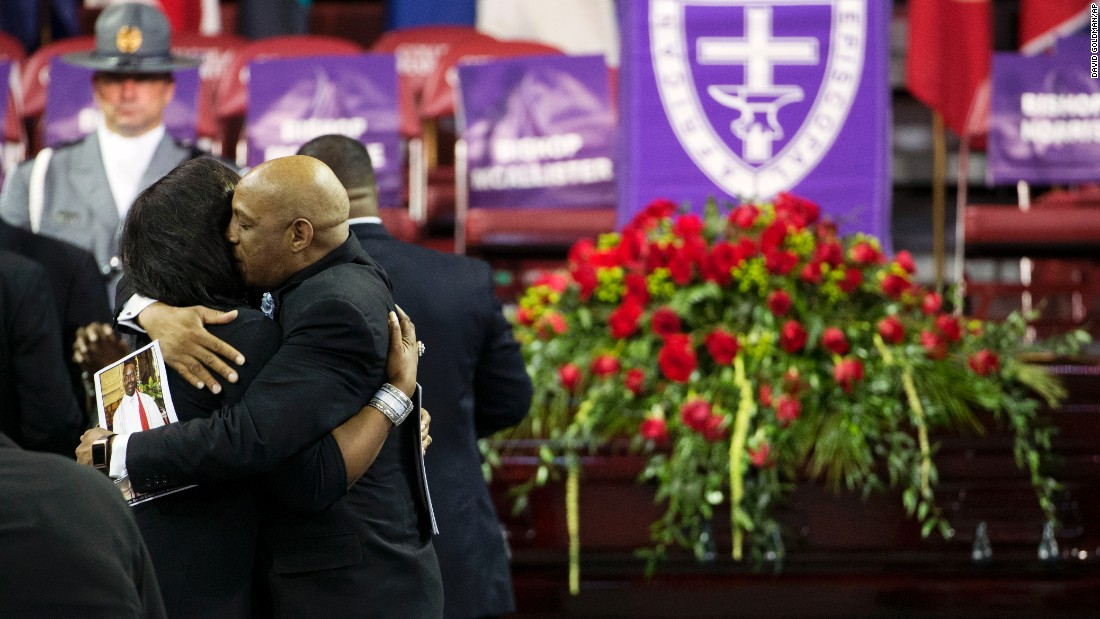 Mourners embrace next to Pinckney's casket.