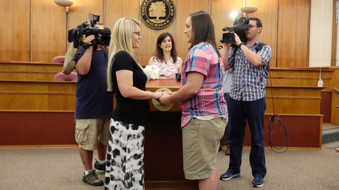 Oakland County Clerk Lisa Brown, center, marries Breanne Brodak, left, and Cortney Tucker in Pontiac, Michigan, on June 26.